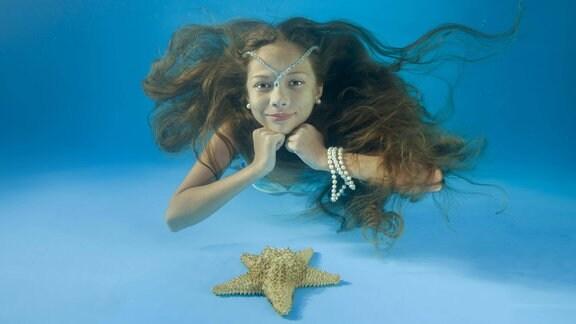 Mädchen mit langen Haaren schaut unter Wasser in die Kamera