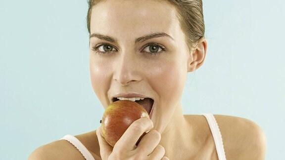 Frau isst einen Apfel
