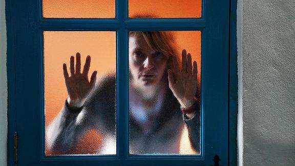 Frau schaut von innen durch ein Fenster