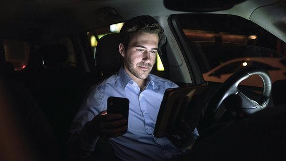 Mann mit Smartphone und Tablet nachts im Auto