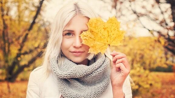 Eine hübsche blonde Frau hält sich ein Herbstblatt vor ihr linkes Auge.