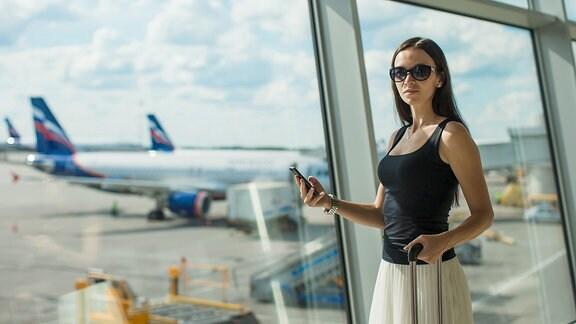 Eine Frau steht auf dem Flughafen am Panoramafenster