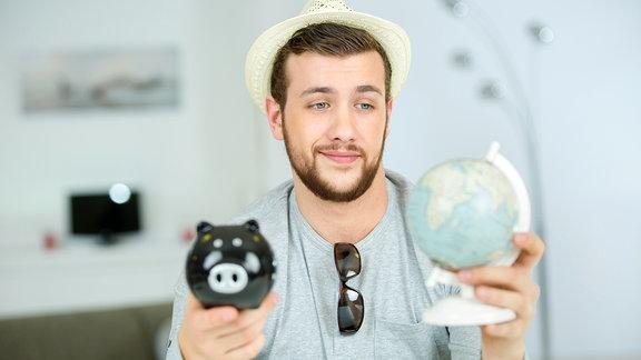 Ein hübscher Mann mit Strohhut hält einen kleinen Globus und ein Sparschwein in seinen Händen