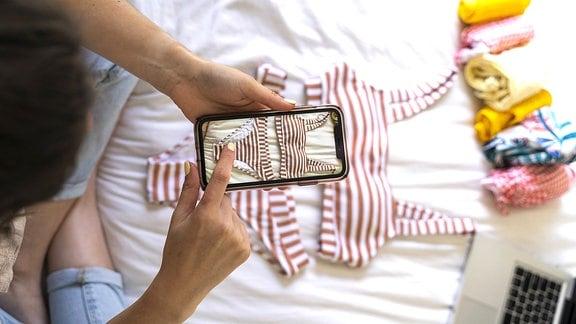 Eine Frau sitzt auf dem Bett und macht mit dem Smartphone ein Foto von einem Bikini
