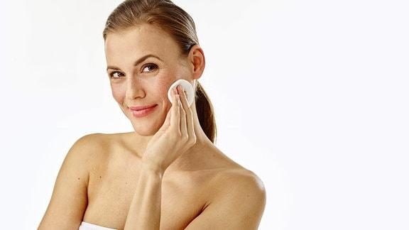 Eine schöne Frau schminkt sich mit einem Wattepad ab