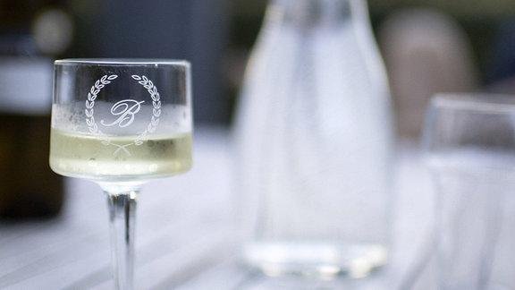 Glas mit Gravur gefuellt mit Weisswein