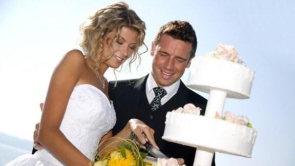 Brautpaar schneidet Hochzeitstorte an.