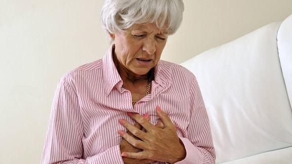 Seniorin hält sich vor Schmerzen die Hände an die Brust