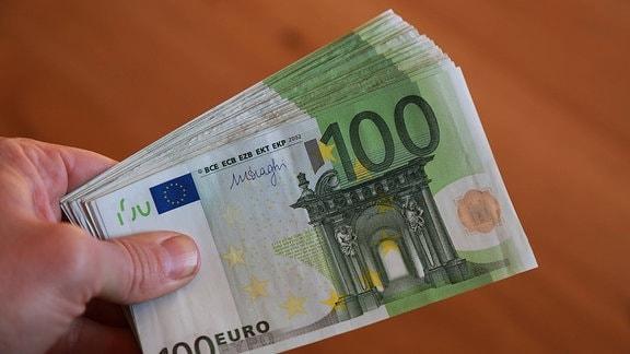 Eine Hand hält ein Bündel Hundert-Euro-Noten