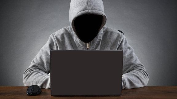 Gesichtsloser Mann im Hoodie am Laptop