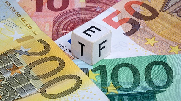 Würfel mit ETF und Geldscheinen.