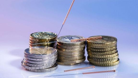 Akupunkturnadeln und Münzen.