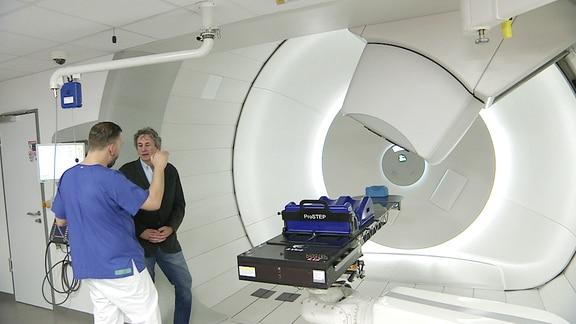 Ein Patient spricht in einem Raum für Protonentherapie mit einem Arzt.