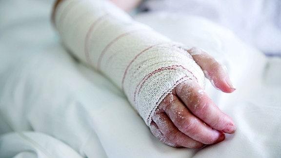 Eine verbundene Hand liegt auf einer weißen Bettdecke.