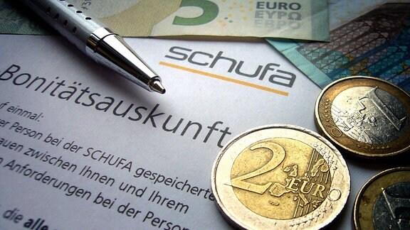 Geldscheine, Münzen, Kugelschreiber auf Schufa-Bonitätsauskunft