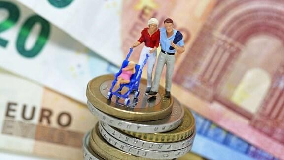 Modellfiguren, die eine junge Familie darstellen auf einem Münzenstapel vor Geldscheinen.