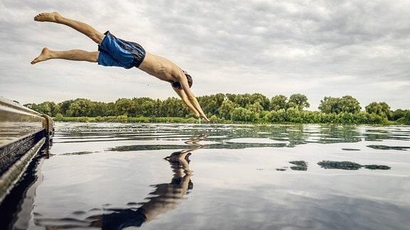 Junger Mann springt von einem Steg in einen See.