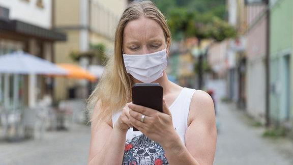 Eine junge Frau mit Mund-Nasen-Behelfs-Schutz schaut in einer Fußgängerzone auf ihr Handy.