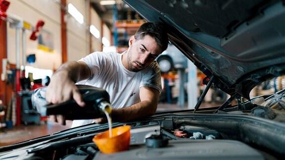 Mechaniker füllt Öl nach.