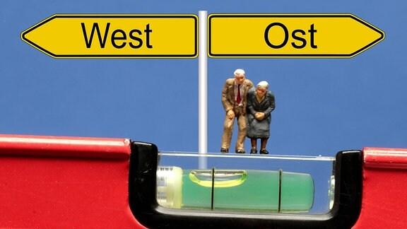 Symbolbild Ungleichgewicht bei Rentenentwicklung in Ost und West: Senioren stehen auf der schiefen Ebene einer Wasserwaage