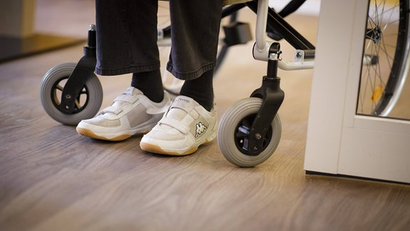 Füße eines Mannes, der im Rollstuhl sitzt
