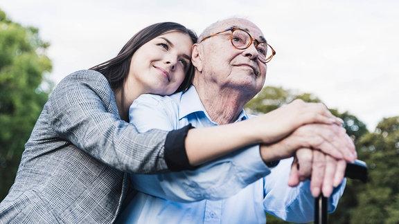 Eine junge Frau sitzt mit ihrem Opa auf einer Parkbank.