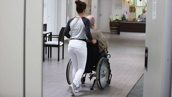 Vorstellung Besuchszimmer in städtischen Pflegeeinrichtungen. Eine Pflegerin schiebt einen alten Mann im Rollstuhl.