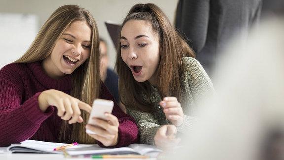 Zwei Mädchen schauen sich etwas auf dem Smartphone an und lachen.
