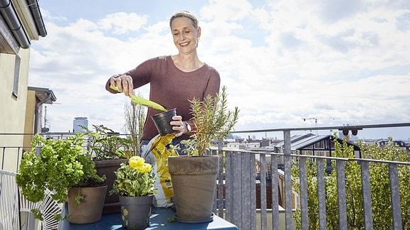 Eine Frau kümmert sich um die Kräuter auf ihrem Balkon.