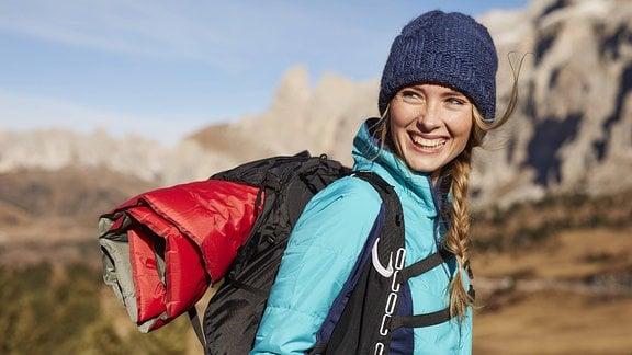 Frau beim Wandern mit Rucksack und einer selbstaufblasenden Isomatte