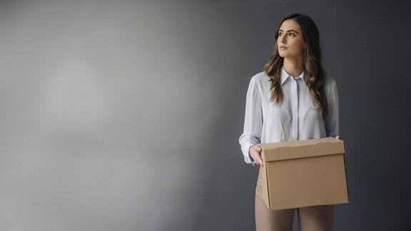 Eine ernst blickende, junge Businessfrau hält einen Karton in ihren Händen, während sie vor einer grauen Wand steht.
