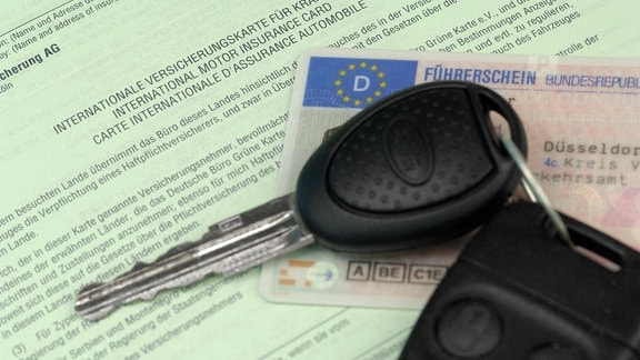 Autoschlüssel und Führeerschein auf grüner Versicherungskarte