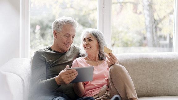Glückliches Seniorenpaar entspannt sich zu Hause auf der Couch und nutzt das Tablet zum Online-Shopping