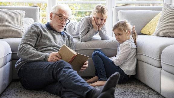 Opa liest Enkelkindern eine Geschichte vor.