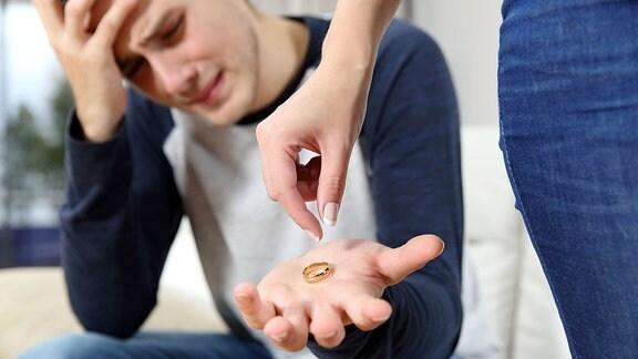 Eine Frauenhand lässt einen Ehering in die Hand eines Mannes fallen.