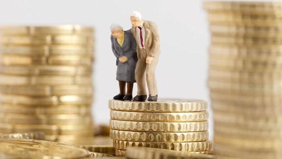 Modellfiguren eines Rentnerpaares in gebeugter Haltung auf einem Stapel Eurocent-Münzen.