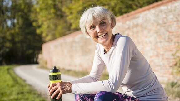sportliche Rentnerin auf einer Bank