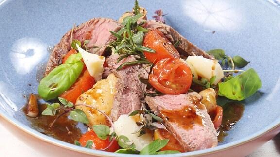 Blauer Teller mit einem Fleischgericht