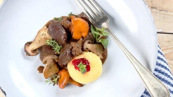 Teller mit Wild und Pilzen