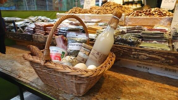 Flechtkorb mit Lebensmitteln auf einem Marktstand.