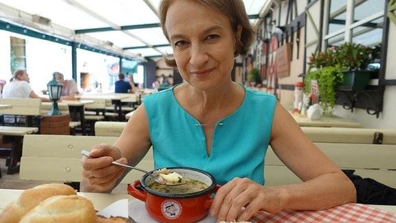 Frau in blauem Kleid posiert mit Suppentöpfchen.