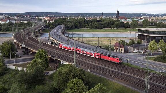 Eine S-Bahn zwischen den Bahnhöfen Dresden-Neustadt und Hauptbahnhof. Der Zug hat gerade die Elbe überquert. Am rechten Bildrand ein Teil des sächsischen Parlamentsgebäudes. S-Bahn in Dresden.
