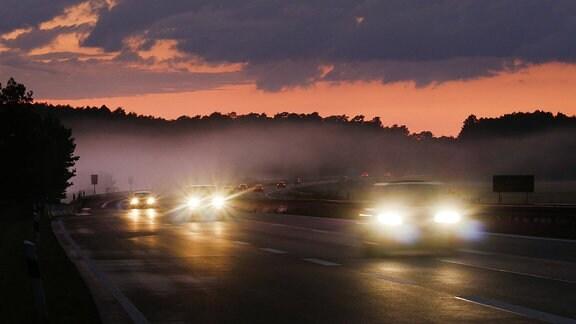 Verkehr auf der Autobahn bei Sonnenuntergang und einem Nebelfeld.