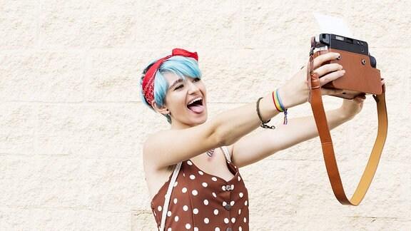 Junge Frau mit blauen Haaren macht ein Selfie mit einer Sofortbildkamera.