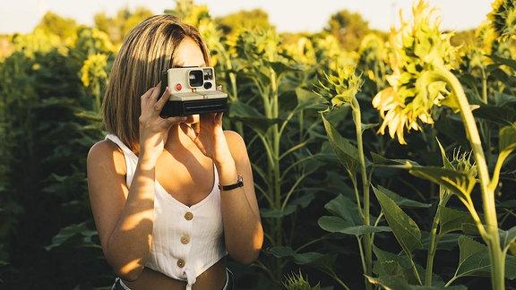 Junge Frau fotografiert mit einer Sofortbildkamera.