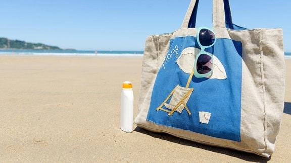 Sonnencreme, Badetasche, Sonnebrille am Strand