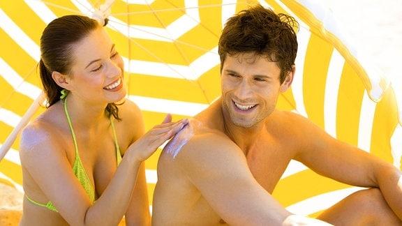 Eine Frau reibt ihren Freund mit  Sonnencreme ein.