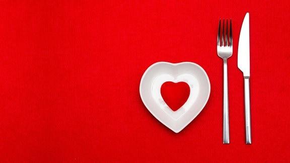 Teller in Herzform mit Messer und Gabel vor rotem Hintergrund
