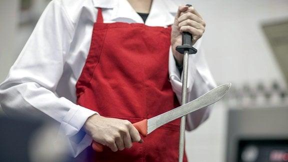 Schlachter wetzt sein Messer.