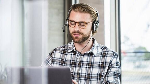Ein Mann mit Headset zu Hause am Laptop